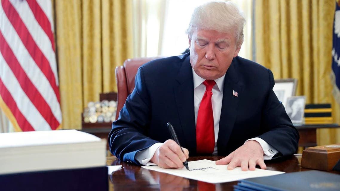 US President Donald Trump signs the $1.5 trillion tax overhaul plan in the Oval Office of the White House in Washington, on December 22, 2017. (Reuters)
