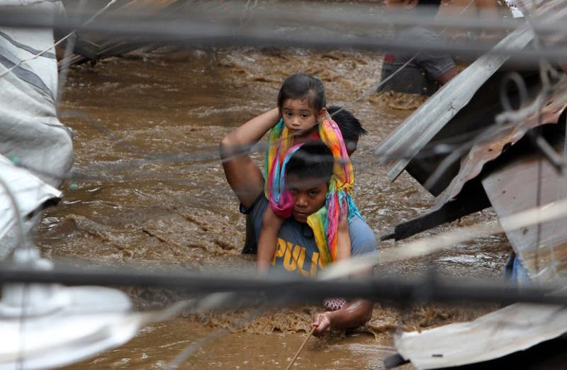 A policeman carries a young girl as he wades through a flooded street in Cagayan City. (AFP)