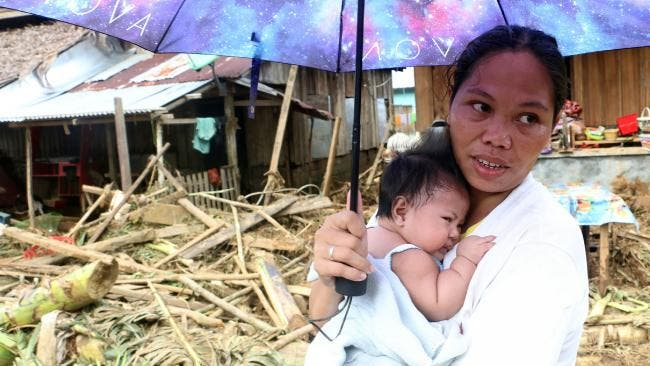A woman stands with her baby in front of damaged houses and fallen trees in Barangay San Mateo Borongan in eastern Samar. (AFP)