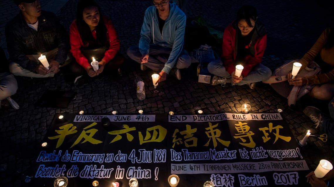 Demonstrators hold a candle-lit vigil in front of Berlin's Brandenburg Gate on June 4, 2017, to commemorate China's crackdown on pro-democracy protesters in Tianamen Square on June 4, 1989. (AFP)