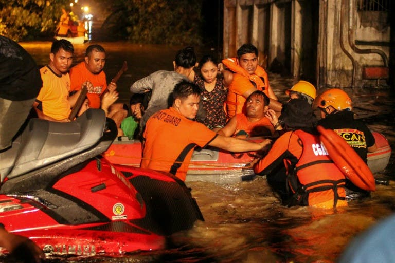 Rescue workers evacuate flood-affected residents in Davao on the southern Philippine island of Mindanao early on December 23, 2017, after Tropical Storm Tembin dumped torrential rains across the island. (AFP)