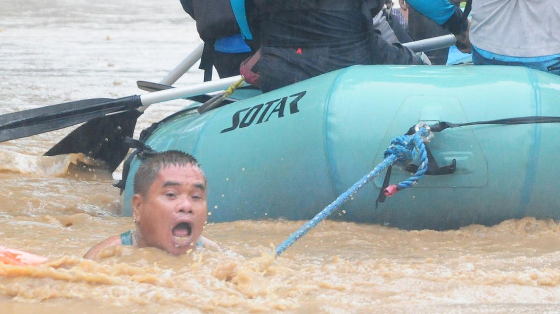 A man clings onto the rope of a rescue boat as residents are evacuated from their homes. (Reuters)