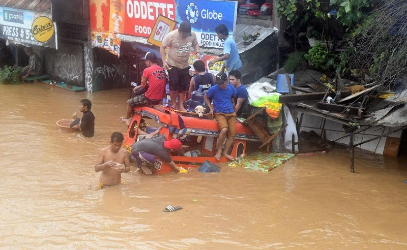 Residents are seen on the top of a partially submerged vehicle along a flooded road in Cagayan de Oro city in the Philippines December 22, 2017. (Reuters)