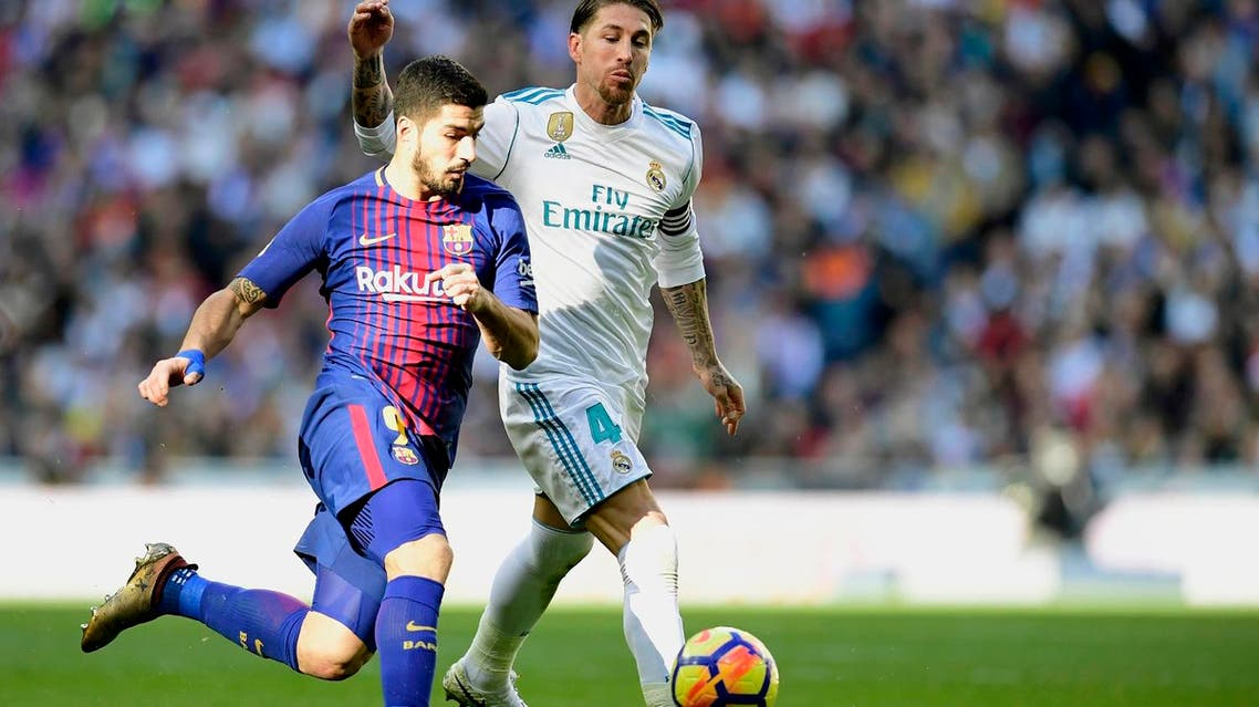 """Barcelona forward Luis Suarez (L) vies with Real Madrid defender Sergio Ramos during the Spanish League """"Clasico"""" football in Madrid on December 23, 2017. (AFP)"""
