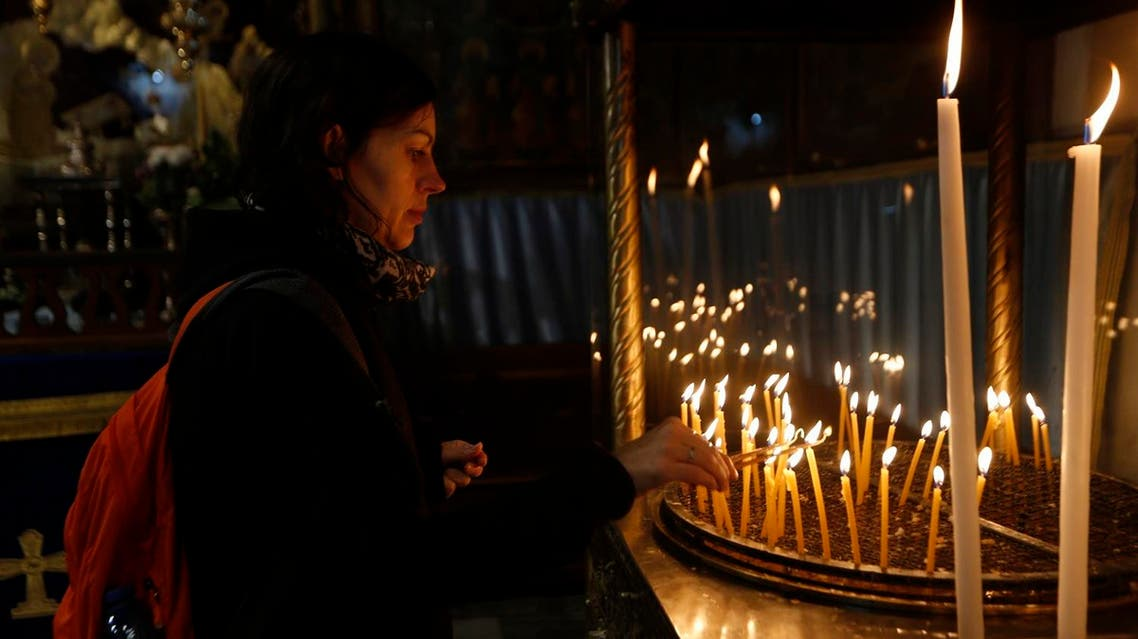 Christian worshiper lights candles at the Church of the Nativity, on Christmas Eve, in the West Bank City of Bethlehem, Sunday, Dec. 24, 2017. (AP)