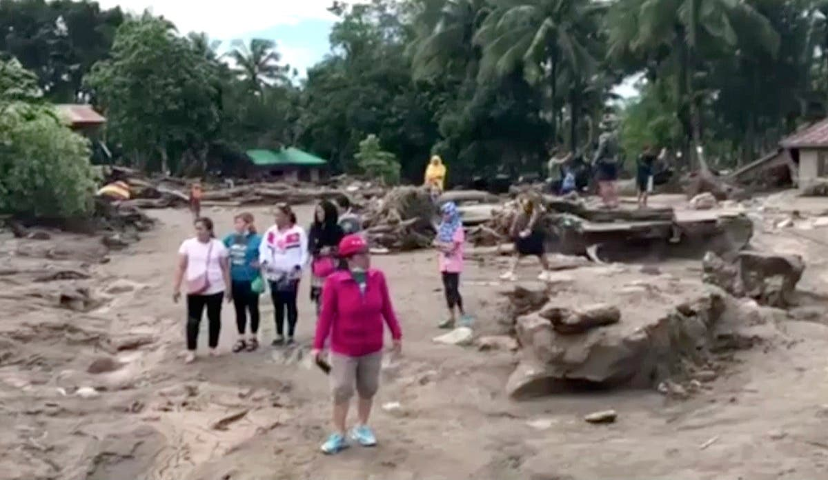 In this image made from video, people stand in the area damaged by storm and resulting floodwaters in Lanao del Norte, southern Philippines, Sunday, Dec. 24, 2017. (AP)