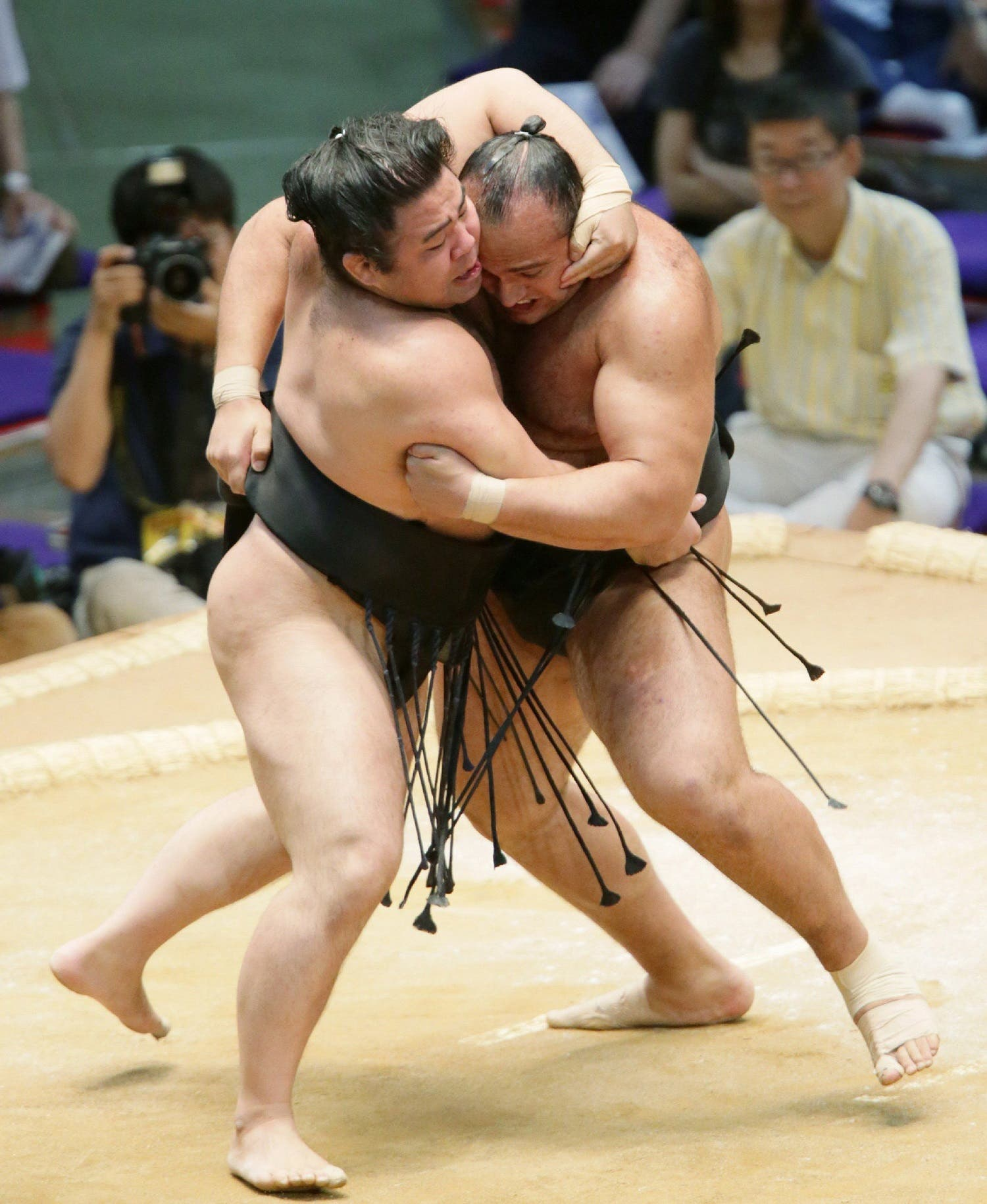 Osunaarashi pushes Satoyama (L) out of the ring during the second-day bout of the Nagoya Grand Sumo Tournament in Nagoya on July 8, 2013. (AFP)