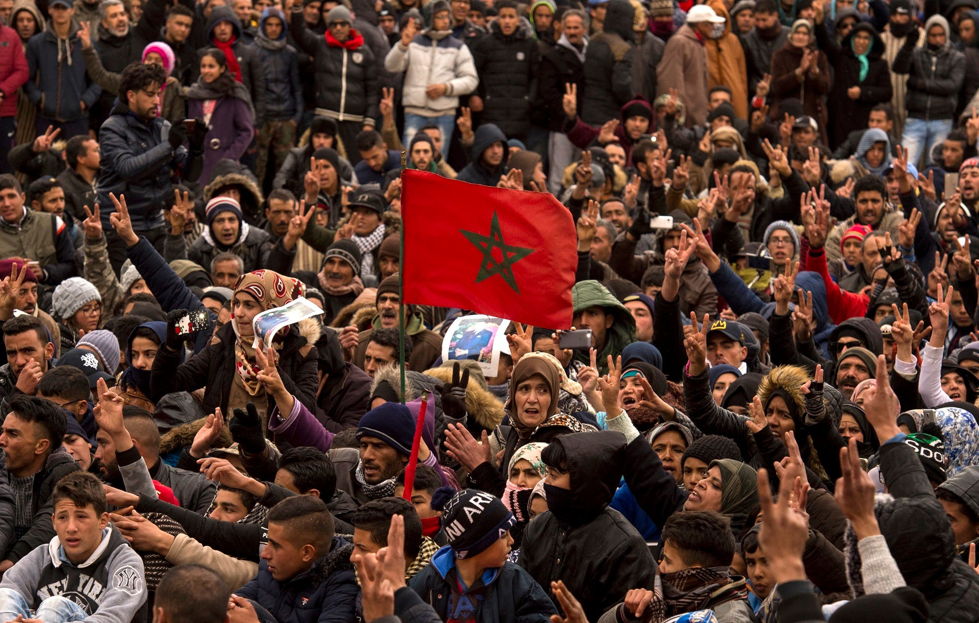 Moroccans shout slogans and wave their national flag as they participate in a demonstration after the funeral on December 27, 2017. (AFP)