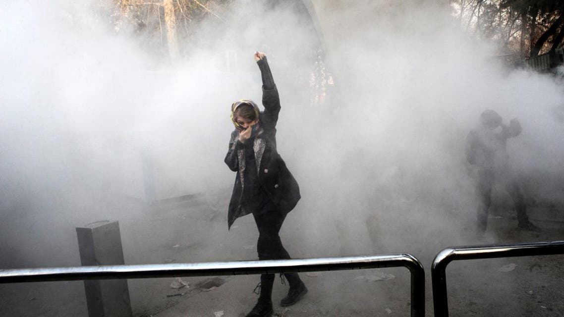 An Iranian woman raises her fist amid the smoke of tear gas at the University of Tehran during a protest. (AFP)