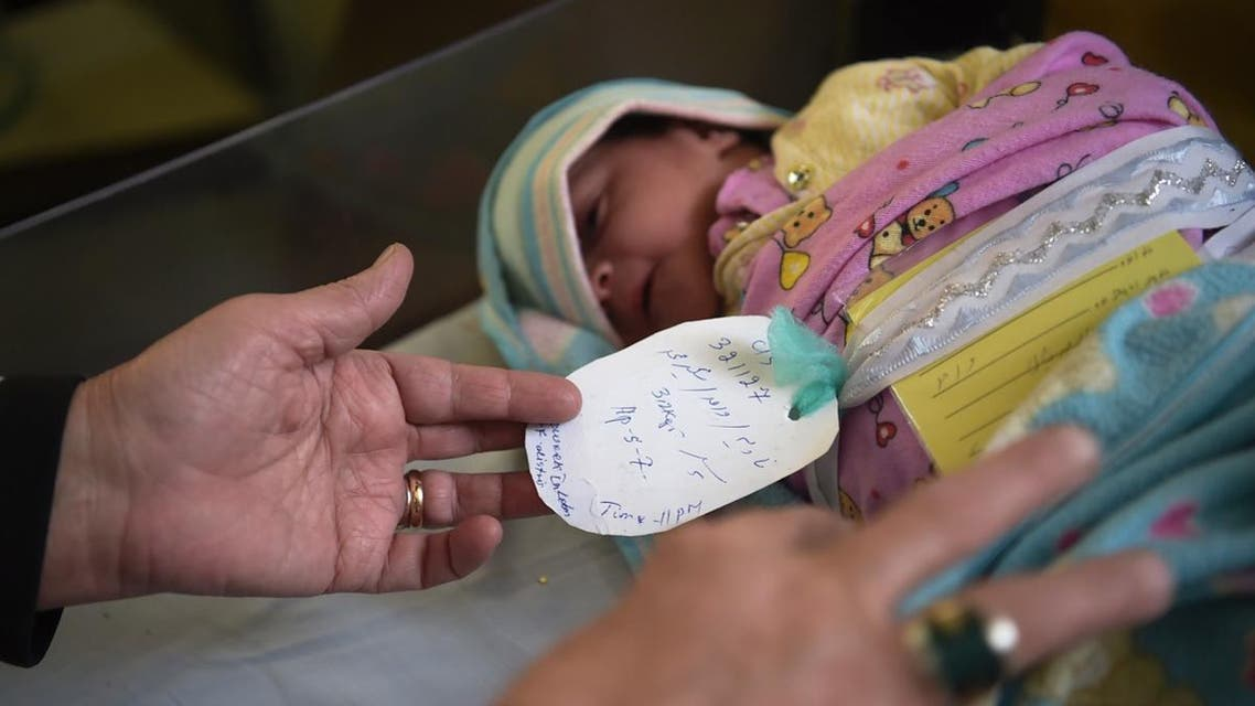 An Afghan paediatric trainee inspecting the tag on a newborn baby at a maternity ward in the Malalai Maternity Hospital in Kabul. (AFP)