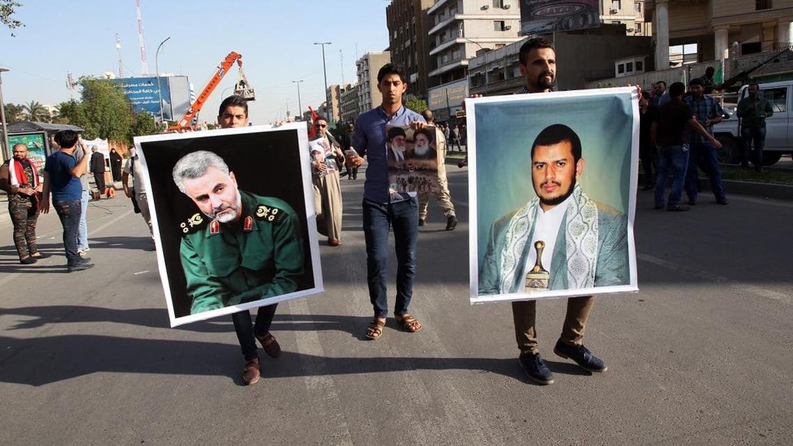 An Iraqi holds a portrait of Shiite Huthi rebels' leader in Yemen, Abdulmalik al-Huthi (R) and General Qassem Suleimani (L), the commander of the Quds Force, the foreign operations arm of Iran's Revolutionary Guards. (AFP)