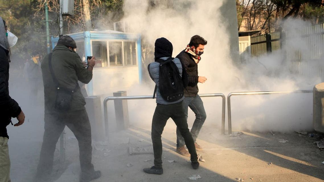 Iranian students run for cover from tear gas at the University of Tehran during a demonstration driven by anger over economic problems. (AFP)