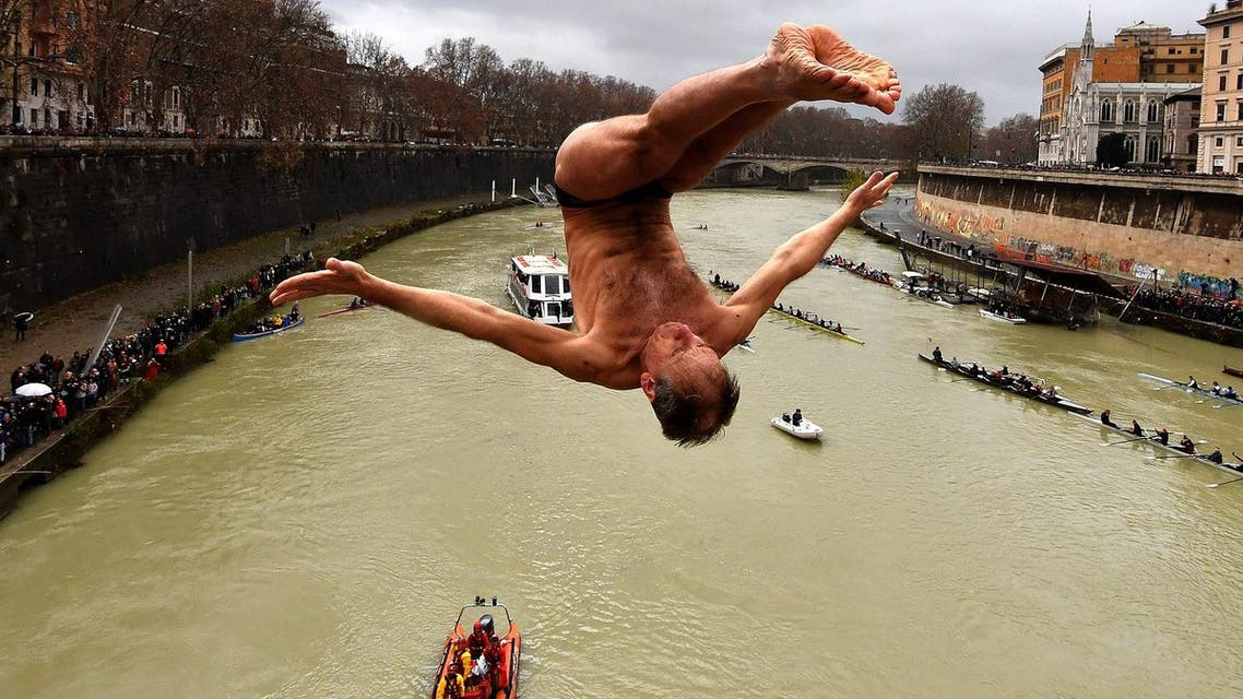 Marco Fois of Italy, dives in the Tiber river as part of traditional New Year celebrations on January 1, 2018 in Rome. (AFP)