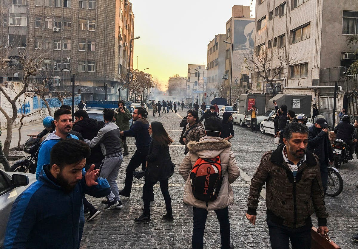 People are affected by tear gas fired by anti-riot Iranian police to disperse demonstrators in a protest over Iran's weak economy, in Tehran, Iran. (AP)