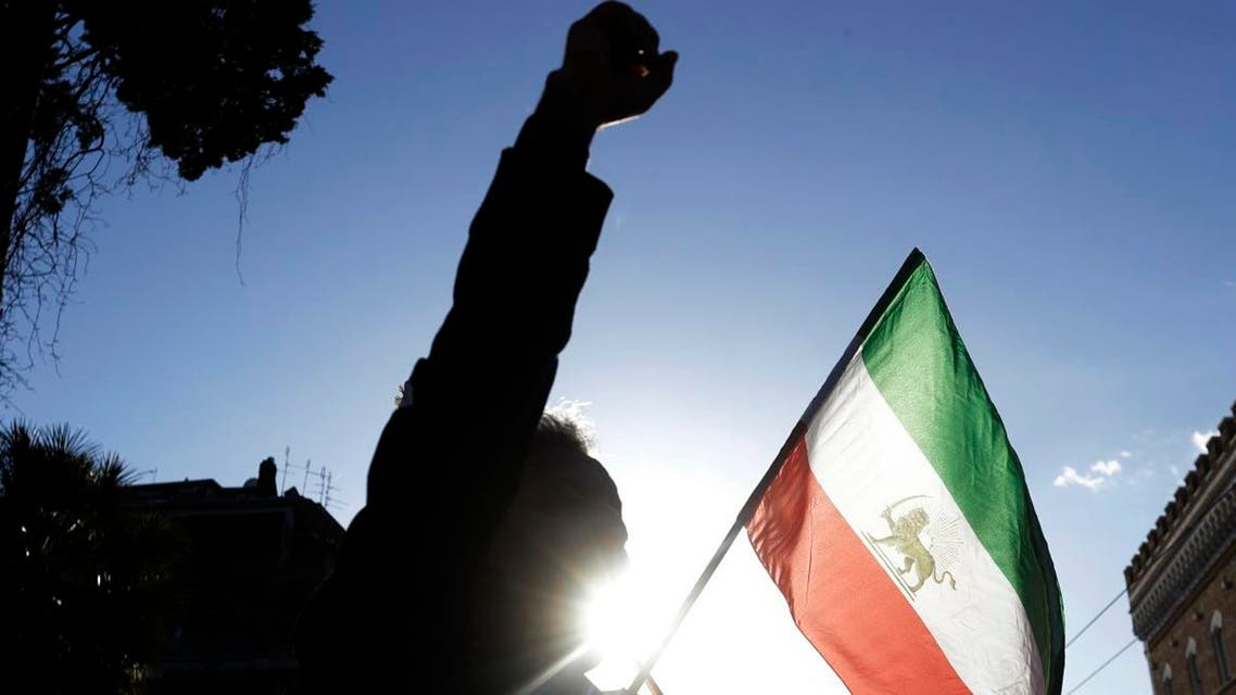 A demonstrator shouts slogans near the flag of the former Imperial State of Iran. (AP)