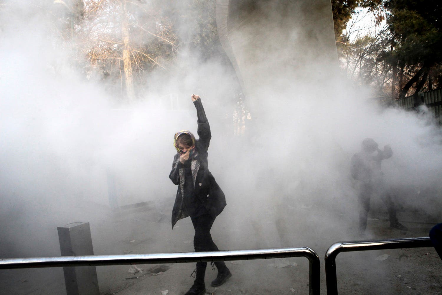 a university student attends a protest inside Tehran University while a smoke grenade is thrown by anti-riot Iranian police, in Tehran, Iran, Saturday, Dec. 30, 2017. (AP)
