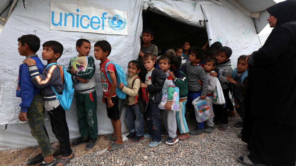 Displaced Iraqi children from the former embattled city of Mosul queue up outside a United Nations Children's Fund school at the Hasan Sham camp, some 40 kilometres east of Arbil in northern Iraq on November 20, 2017. In 2016, UNICEF has helped to get more than 116,000 out of school children back into classrooms, to install pre-fab school structures benefitting 42,000 displaced children, and to distribute school supplies and learning materials to more than 280,000 children. Iraq's second city, Mosul was recaptured in July after being taken in a lightning summer 2014 offensive by the Islamic State group. SAFIN HAMED / AFP