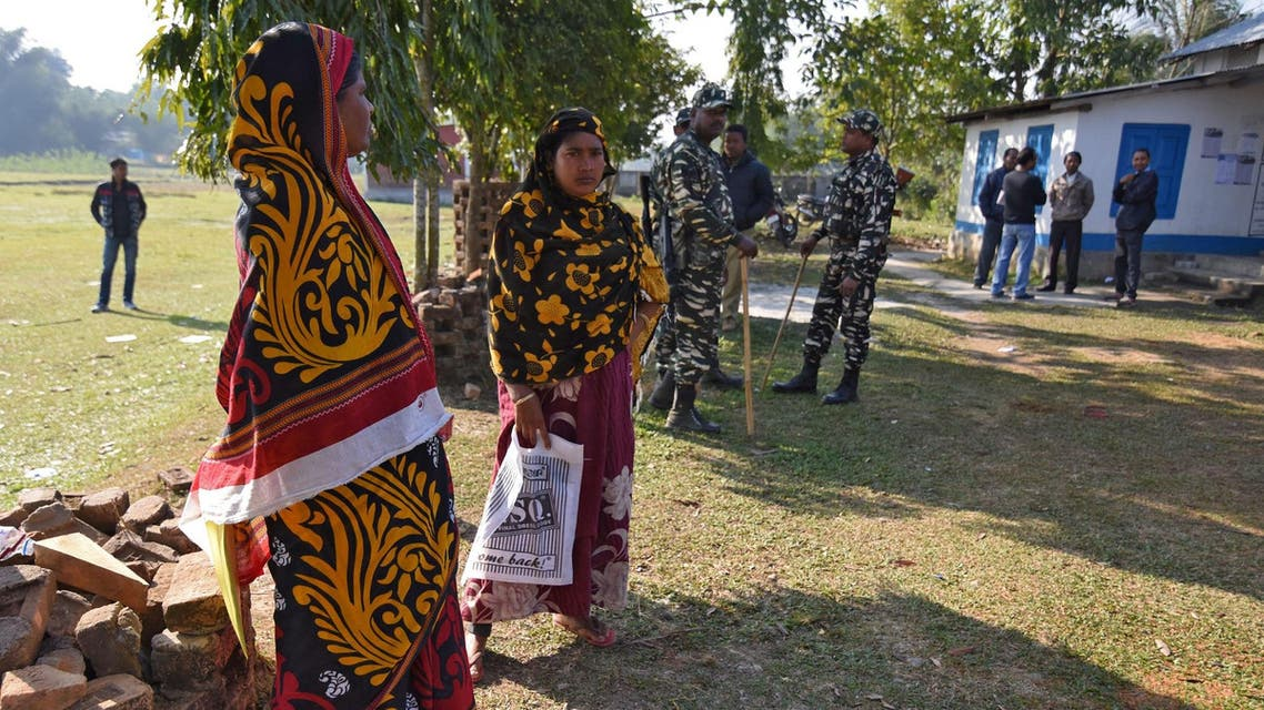 Women stand next to policemen as they wait to check their names on the draft list of the National Register of Citizens in Chandamari village of Goalpara district in Assam on January 2, 2018. (Reuters)