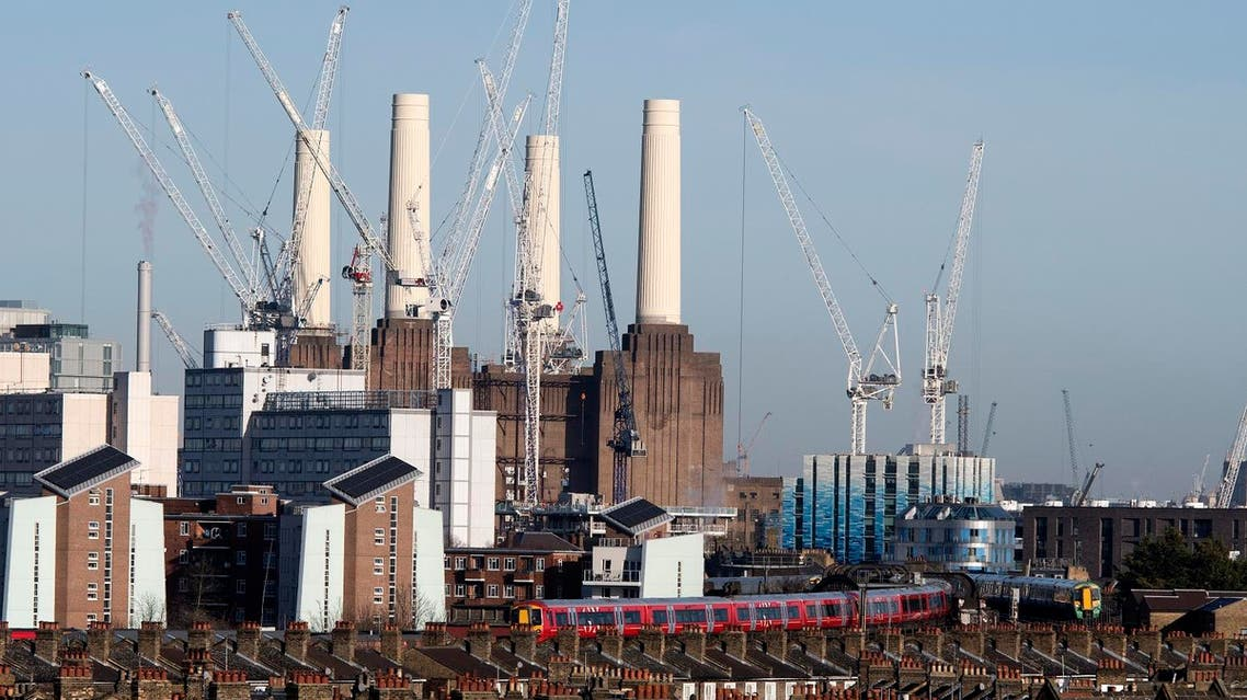 Passenger trains pass through Battersea Park rail station as construction work continues on the Battersea Power Station residential and retail development complex in south-west London on December 18, 2017. (AFP)