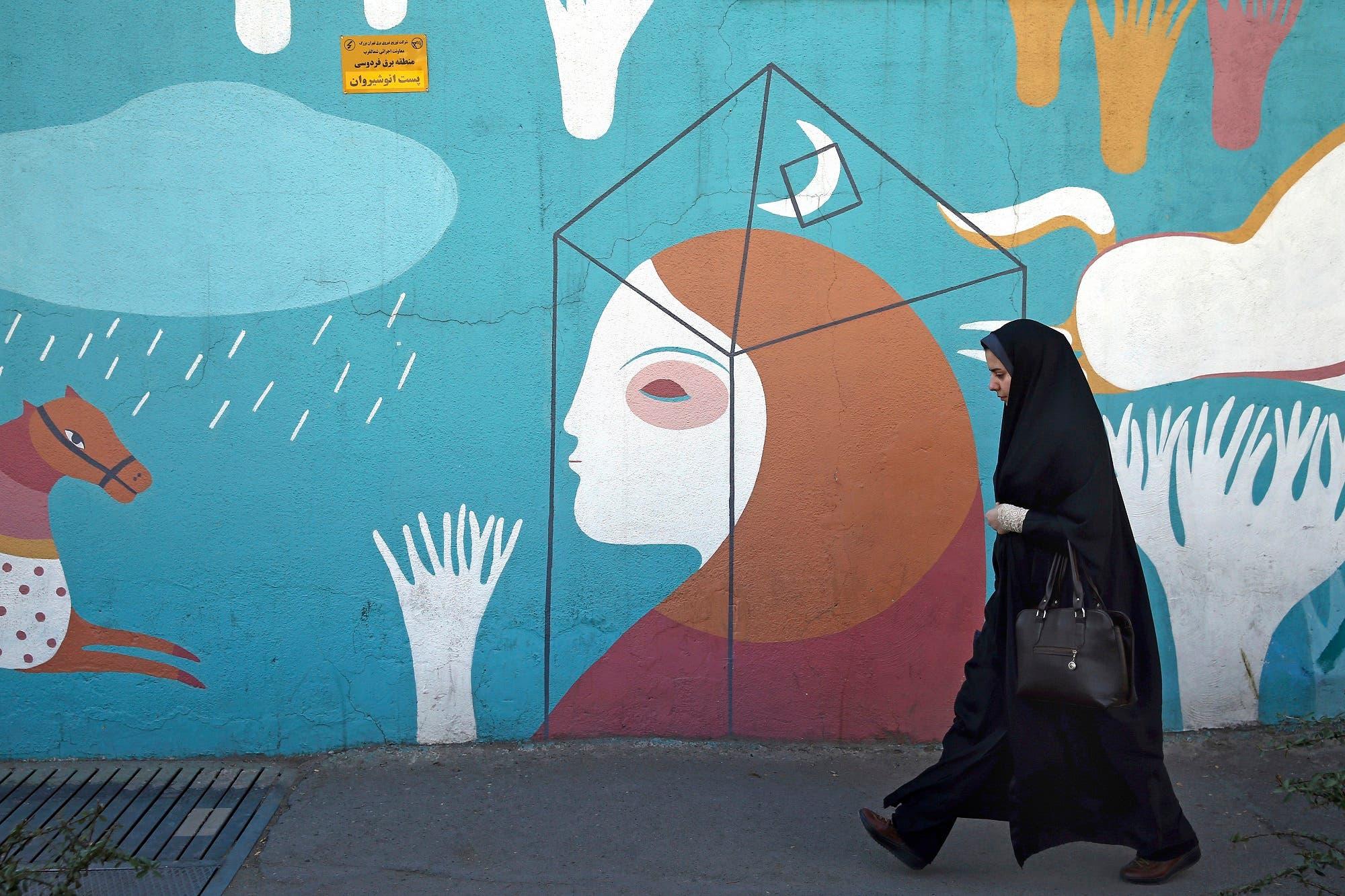 A woman walks past a mural in downtown Tehran, Iran, Wednesday, Jan. 3, 2018. (AP)