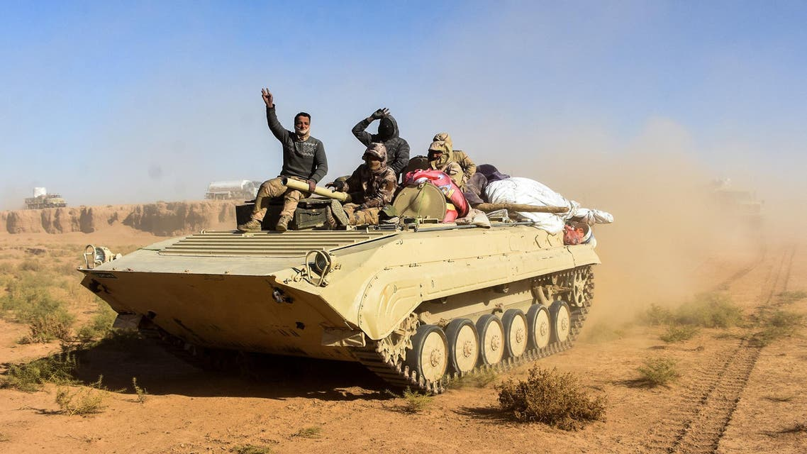Members of the Iraqi forces and the Hashed al-Shaabi (Popular Mobilisation units) wave as they ride on an infanty-fighting vehicle (IFV) near the Iraqi-Syrian border, about 80 kilometres (about 50 miles) west of the border town of al-Qaim on December 9, 2017.  STRINGER / AFP