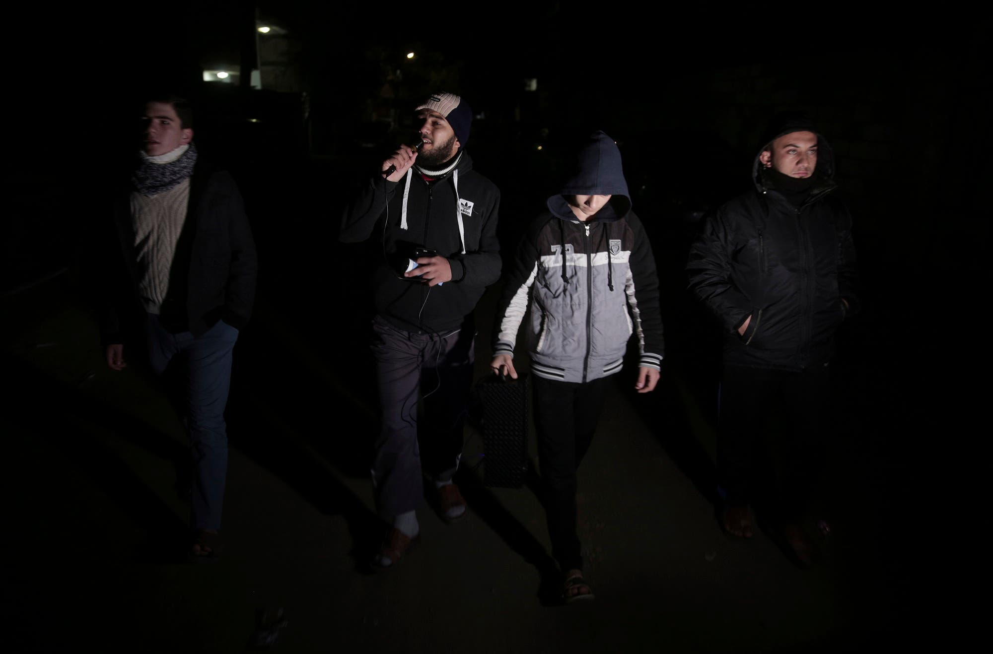 In this Wednesday, Jan. 3, 2018 photo, Palestinian volunteers walk use loadspeakers to call people to wake up for the dawn prayer, in Gaza City. (AP)