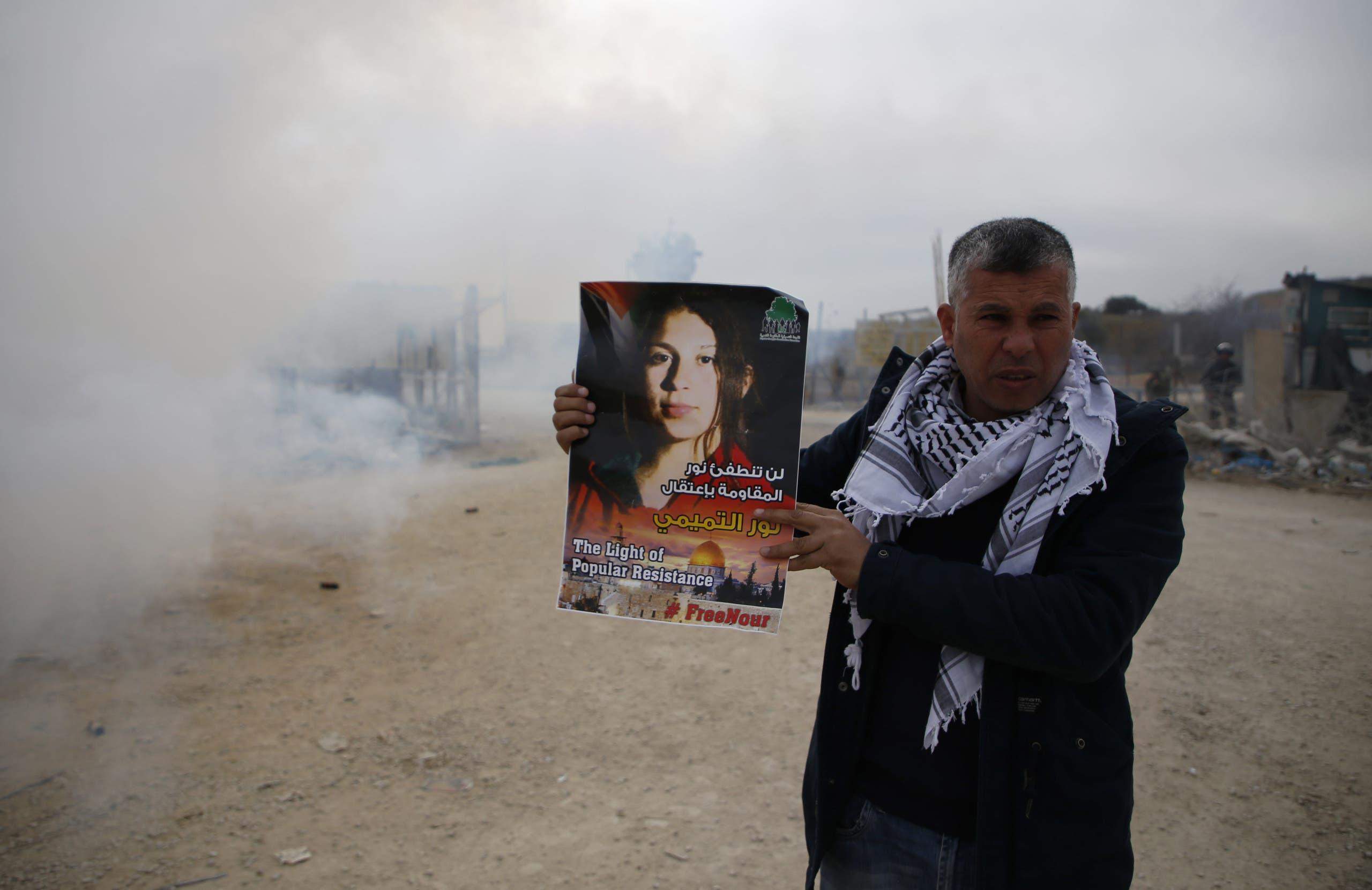 فلسطيني يحمل لافتة تطالب بإطلاق سراح نور التميمي (أرشيفية)
