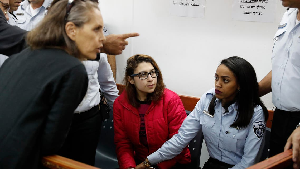 Nour Tamimi (C) who is being detained after a viral video showing her with two members of her family allegedly assaulting two Israeli soldiers is seen in a military court at the Israeli-run Ofer prison in the West Bank village of Betunia on December 28, 2017. The Tamimi family are at the forefront of regular protests in Nabi Saleh, a frequent scene of demonstrations against Israel's occupation of the West Bank. AHMAD GHARABLI / AFP