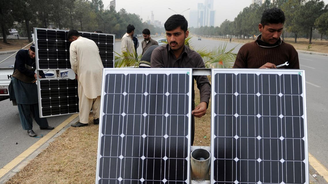Pakistani workers prepare solar energy light panels in Islamabad on February 2, 2014. (AFP)