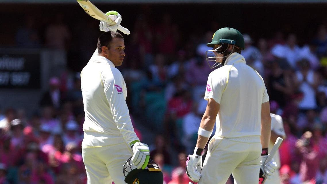 Australia's Usman Khawaja (L) celebrates with teammate Steve Smith (R) after scoring his century against England on the third day of the fifth Ashes cricket Test match in Sydney on January 6, 2018. (AFP)