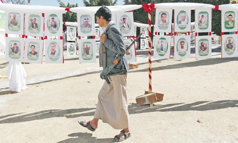 مسلح حوثي يمر بالقرب من صور قتلى الميليشيا في ذمار (أرشيفية)