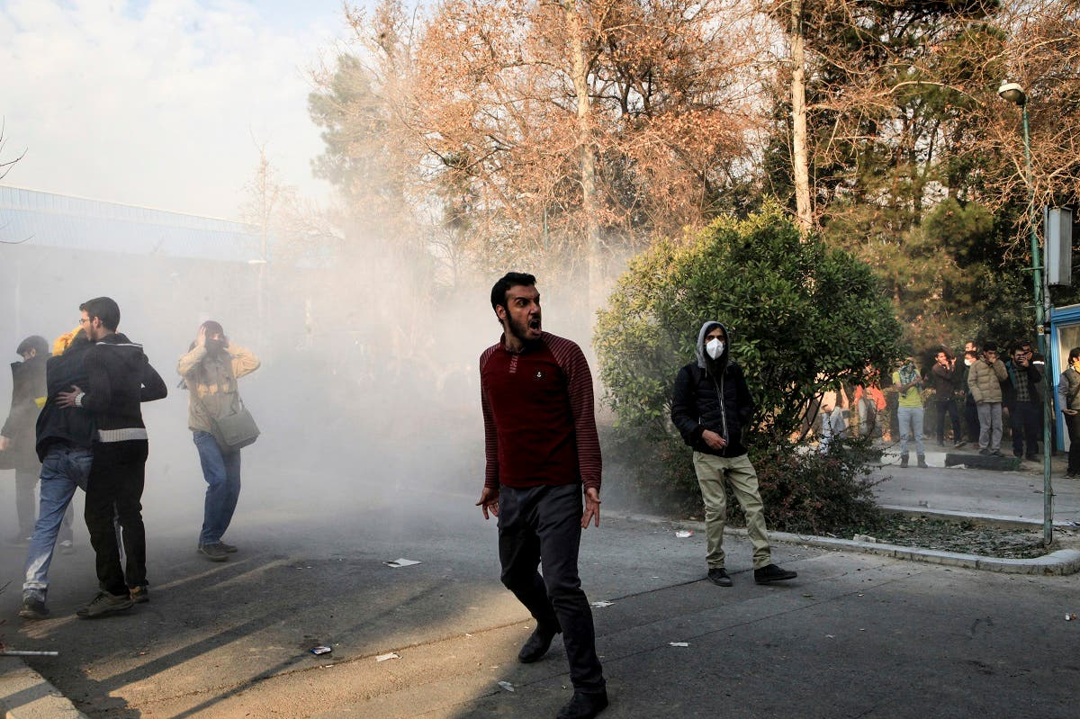 University students attend a protest inside Tehran University while a smoke grenade is thrown by anti-riot Iranian police. (AP)