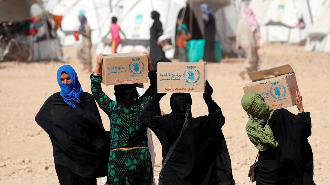 People displaced from fightings between the Syrian Democratic Forces and Islamic State militants carry boxes of food aid given by UN's World Food Programme at a refugee camp in Ain Issa, Syria October 10, 2017. (Reuters)