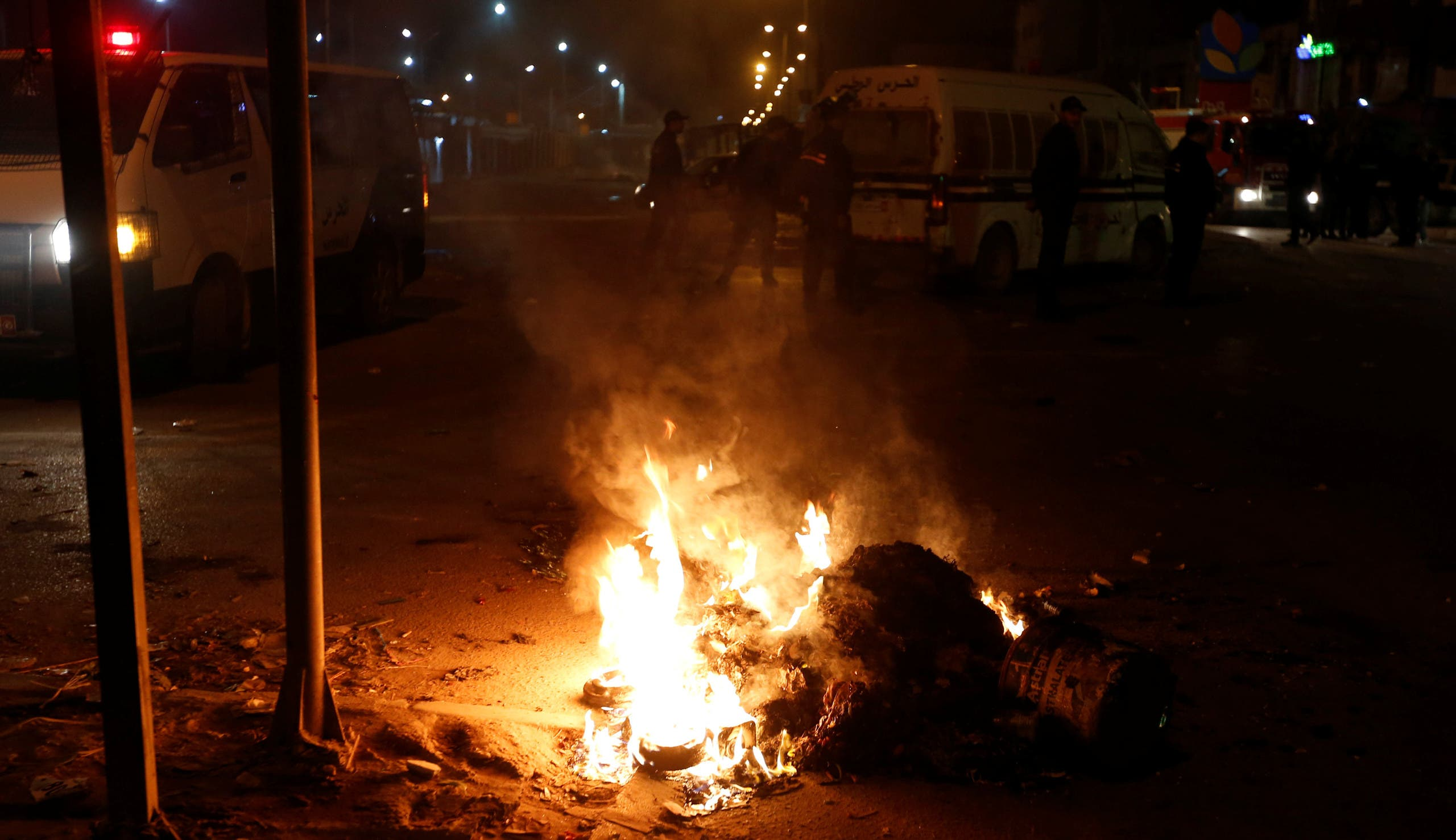 Police vehicles stop in front of burning tires set up by protesters during demonstrations against rising prices and tax increases, in Tunis, Tunisia, January 8, 2018. REUTERS/Zoubeir Souissi