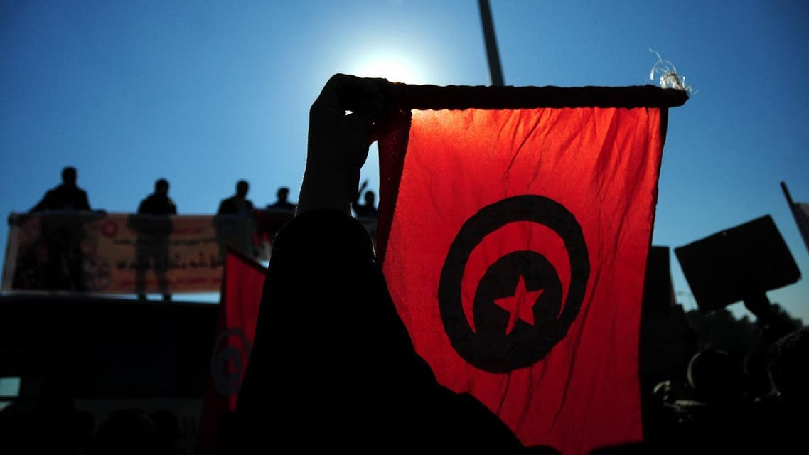 Tunisian police officers wave the national flag and posters as they demonstrate outside the presidential palace in Carthage near Tunis. (AP)