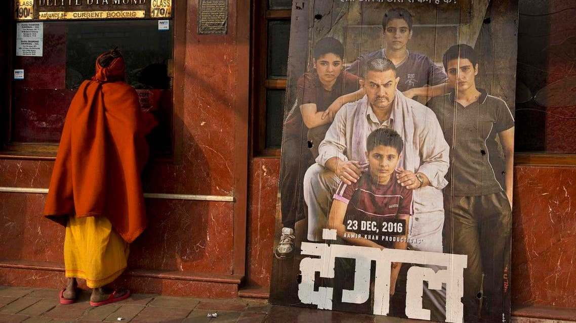 An Indian Sadhu, or Hindu holy man, buys a movie ticket at a counter beside a poster of Bollywood movie Dangal. (AP)