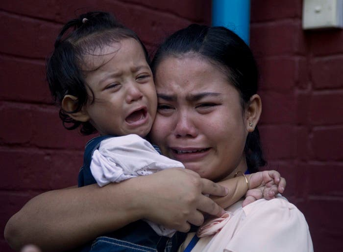 Chit Su Win, wife of detained Reuters journalist Kyaw Soe Oo, cries with her daughter outside the court Wednesday, Jan. 10, 2018, outside Yangon, Myanmar. (AP)