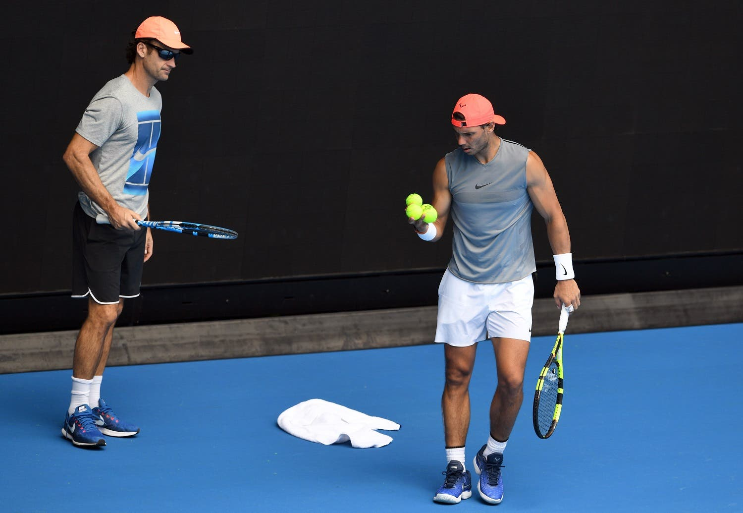 Rafael Nadal of Spain (R) is watched by his coach Carlos Moya (L) during a training session ahead of the Australian Open at Melbourne Park in Melbourne on January 10, 2018. (AFP)