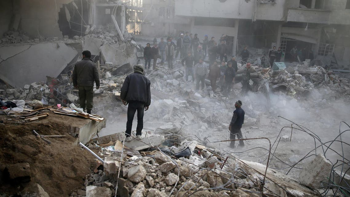 People stand on rubble of damaged buildings, after an airstrike in the besieged town of Hamoria, Eastern Ghouta, in Damascus, Syria Janauary 9, 2018. REUTERS/Bassam Khabieh