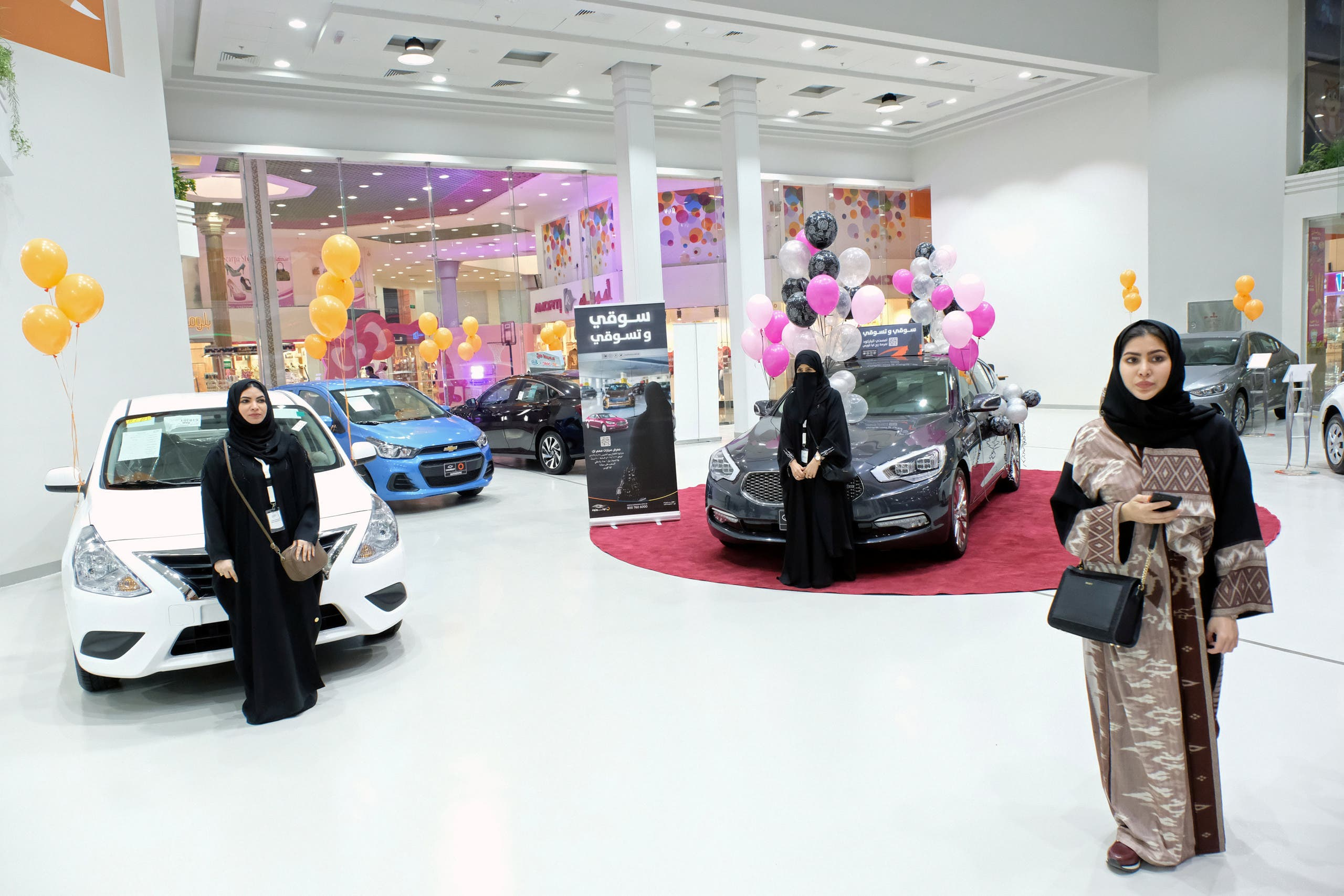 Pink, orange and yellow balloons hung in the mall's showroom as women posed for photos and selfies in front of the cars. (Reuters)