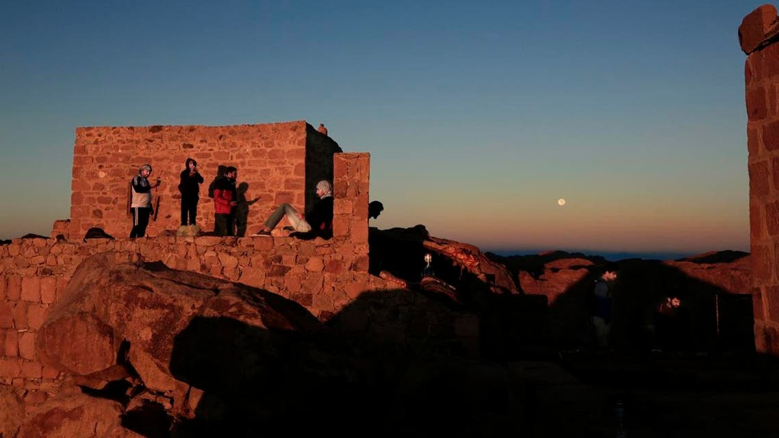 Arab tourists, left and American tourists, right, watch the sun as it rises and the moon as it sets from the view on top Mount Sinai. (AP)