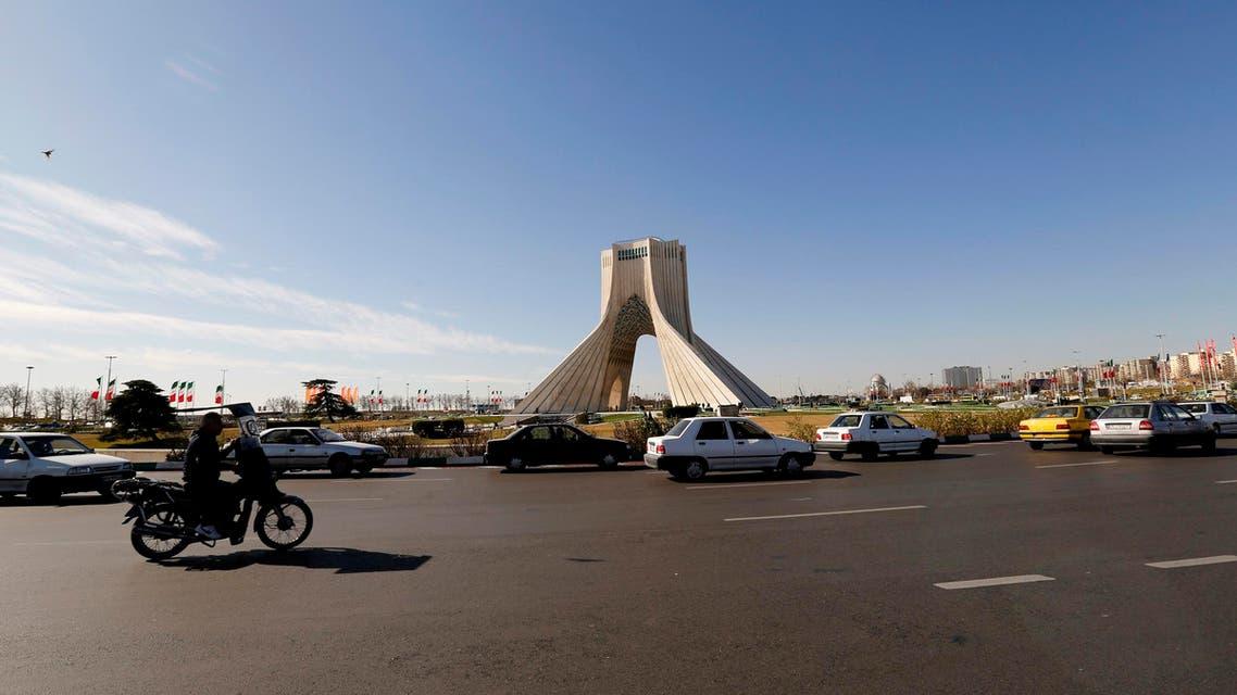 Iranian motorists drive past the Azadi Tower in Tehran on January 13, 2018. (AFP)