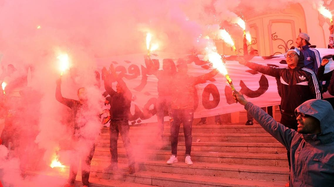 Tunisians carry flares and shout slogans against the government in Tunis. (AFP)