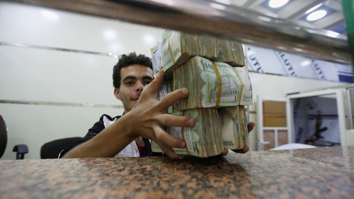 A money changer holds bundles of Yemeni currency at an exchange shop in Sanaa on June 8, 2016. (Reuters)