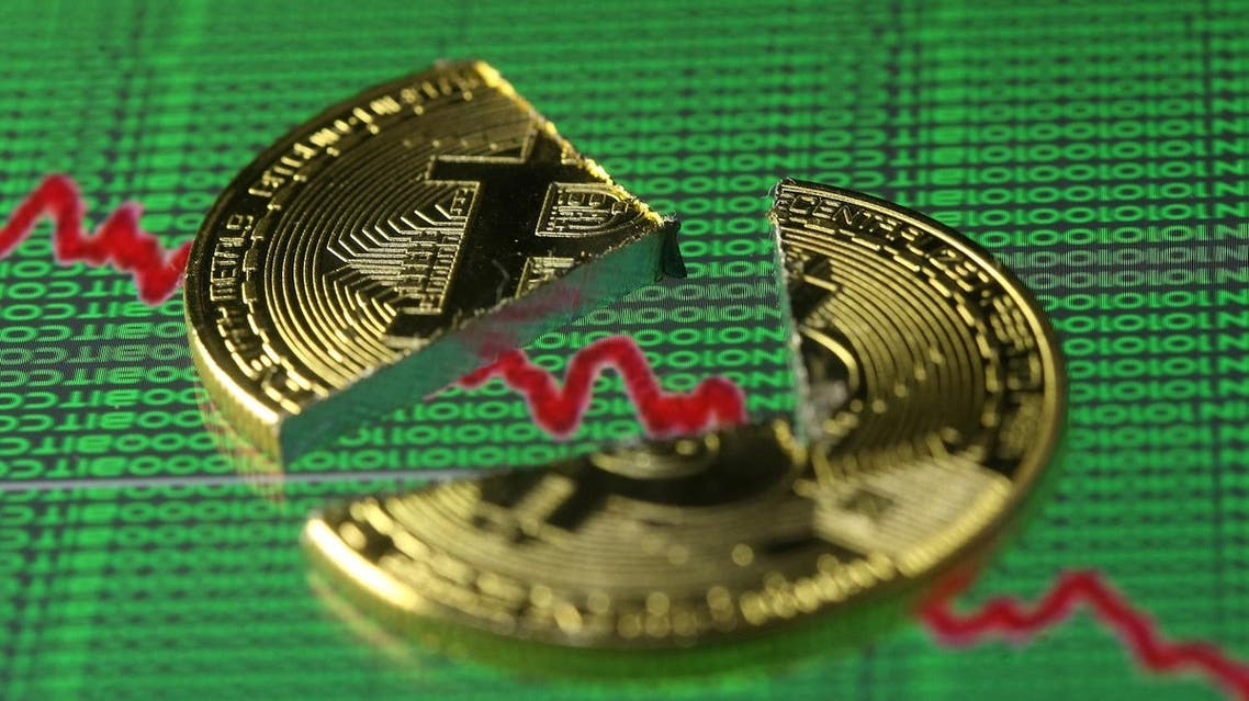 Broken representation of the Bitcoin virtual currency, placed on a monitor that displays stock graph and binary codes, are seen in this illustration picture. (Reuters)