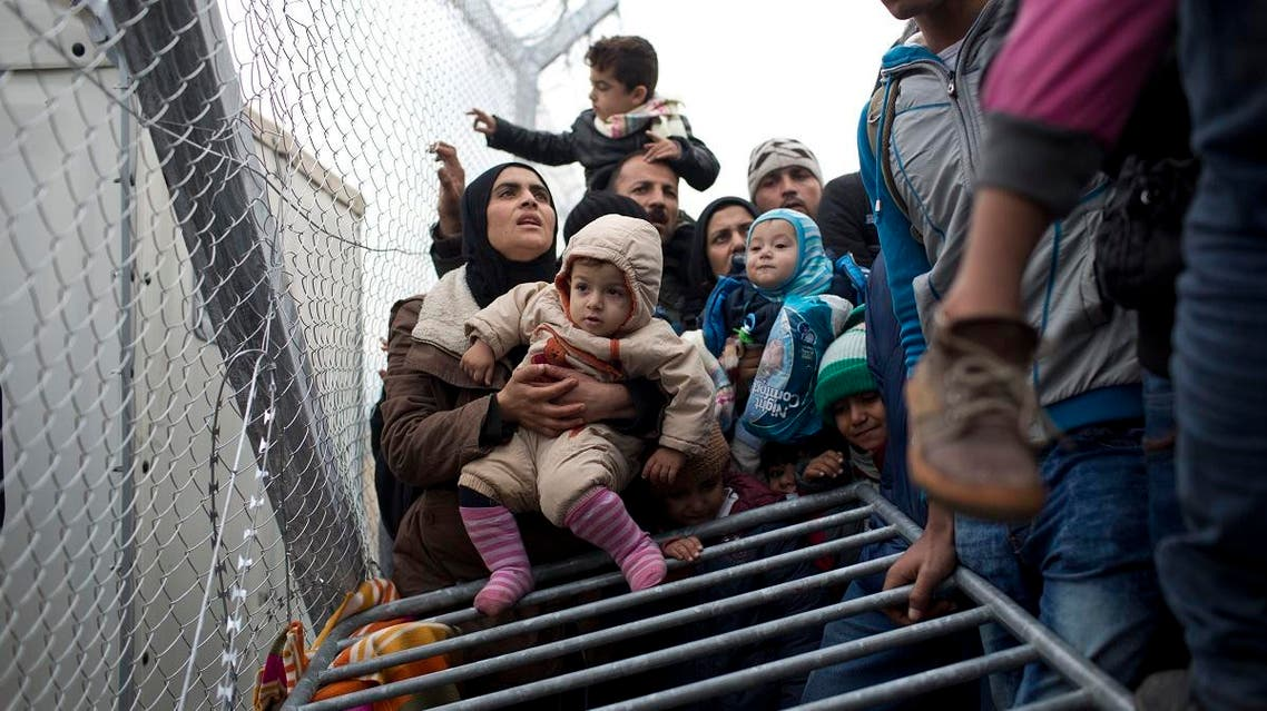 A Syrian family wait along the wire fence that separates the Greek side from the Macedonian one. (AP)