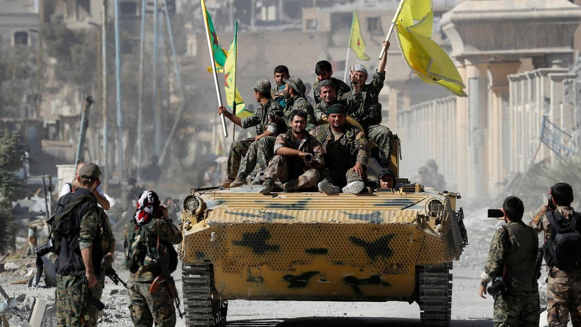 Fighters of Syrian Democratic Forces ride atop of an armored vehicle after Raqqa was liberated from ISIS militants, in Raqqa, on October 17, 2017. (Reuters)