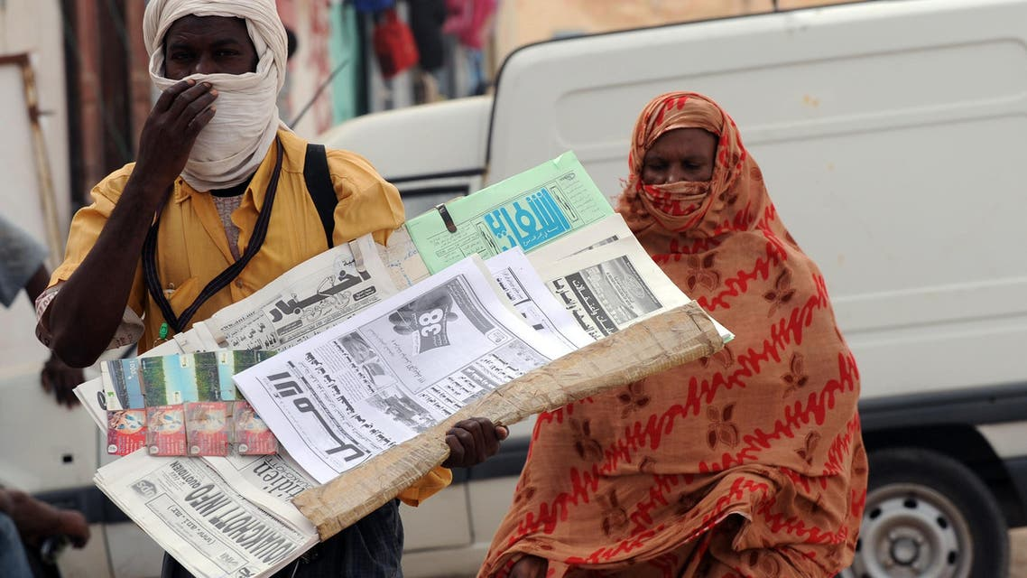 A newspaper seller is followed by a woman on October 6, 2008 in Nouakchott. The leadership has categorically refused international demands for the reinstatement of the president, saying it would not move backwards. The ousted president Sidi Ould Cheikh Abdallahi was the country's first democratically elected president. AFP PHOTO/SEYLLOU SEYLLOU DIALLO / AFP