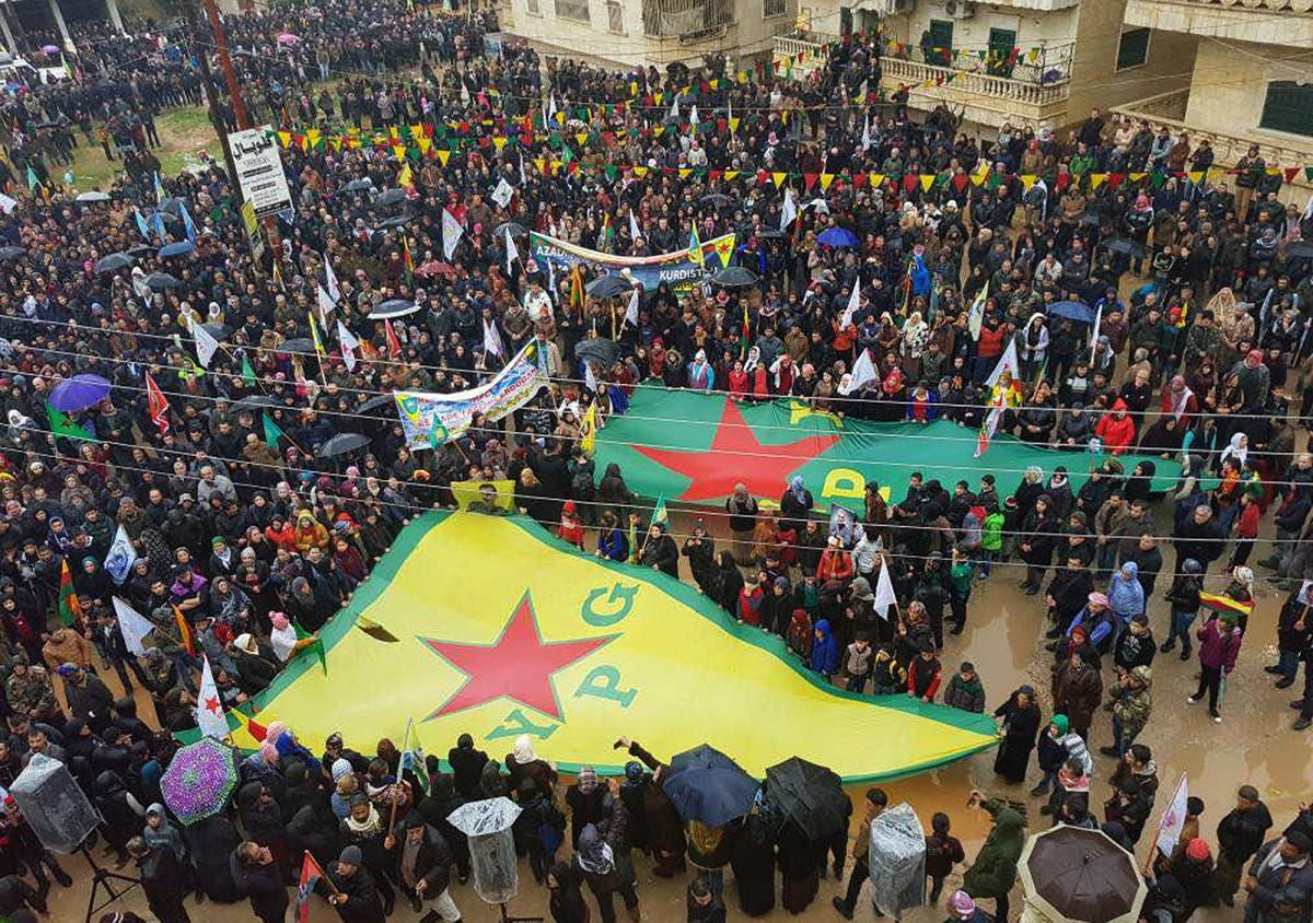 rotesters waving giant flags of the YPG and other parties and militias, during a demonstration against Turkish threats, in Afrin, Aleppo province, north Syria. (AP)