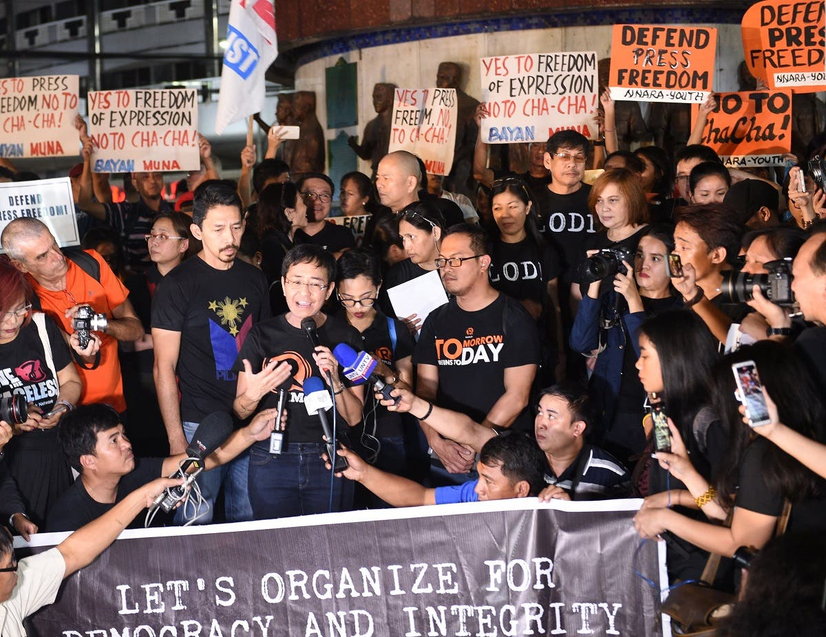 Maria Ressa (centre L-with microphone), the CEO and editor of online portal Rappler, speaks during a protest on press freedom along with fellow journalists in Manila. (AFP)